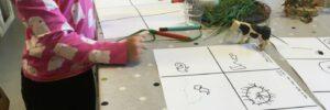 Barnhänder, teckning, plastkossa och gräs