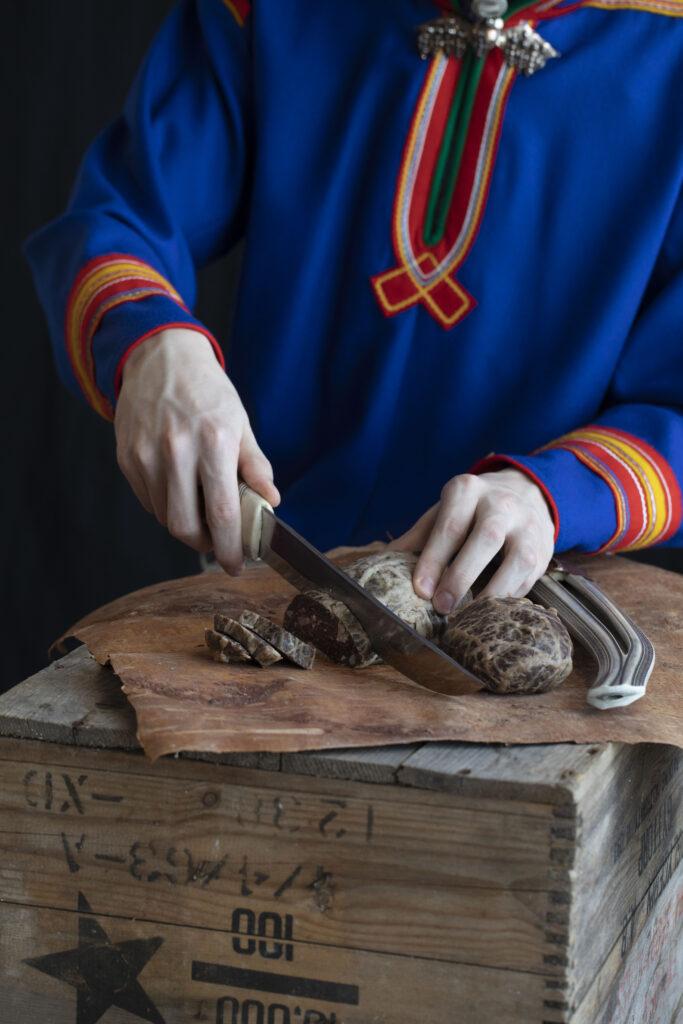 Person i samiska kläder som skär upp renkött