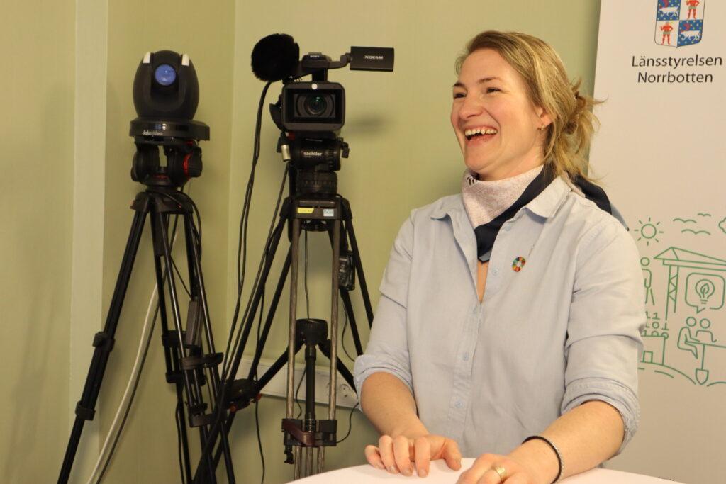 Hulda Wirsén står framför kameror och skrattar