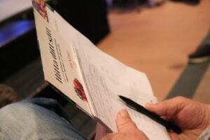 Händer som håller i en broschyr och ett anteckningsblock
