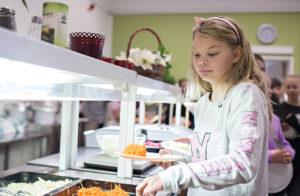 Flicka tar mat i skolmatsal