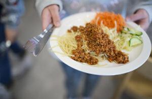 En tallrik med spaghetti med sås, rivna morötter och gurka