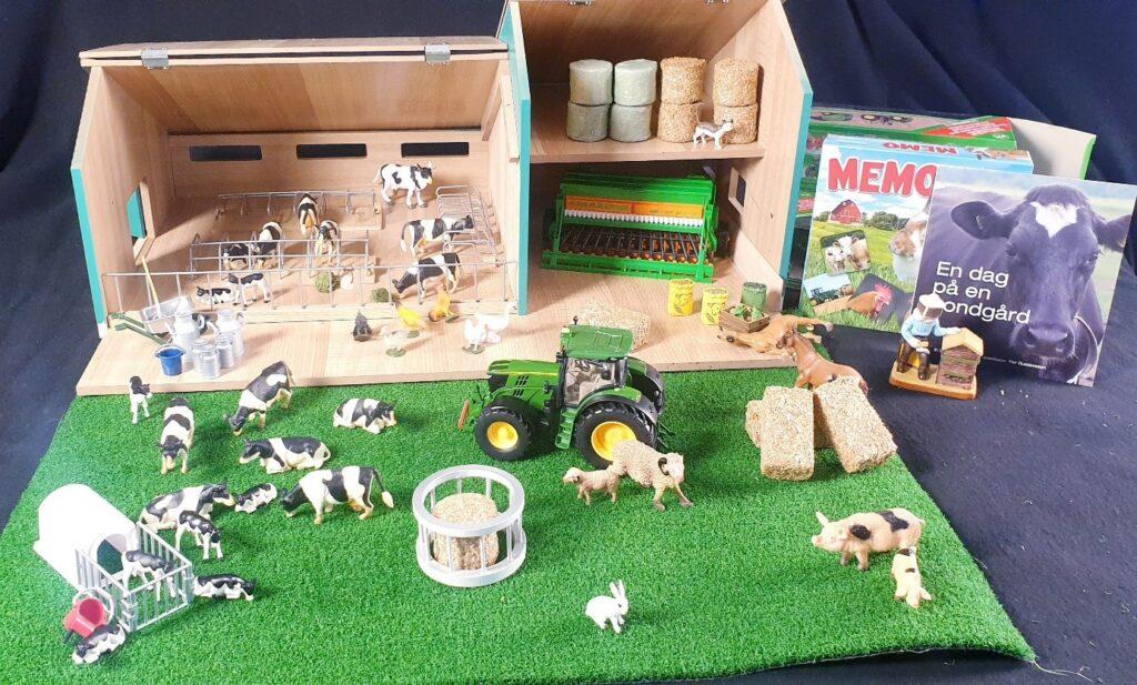 Ett foto på undervisningmaterial bestående av en bondgård i miniatyr byggd i trä, leksaksdjur, böcker om lantbruk, en grön leksakstraktor.