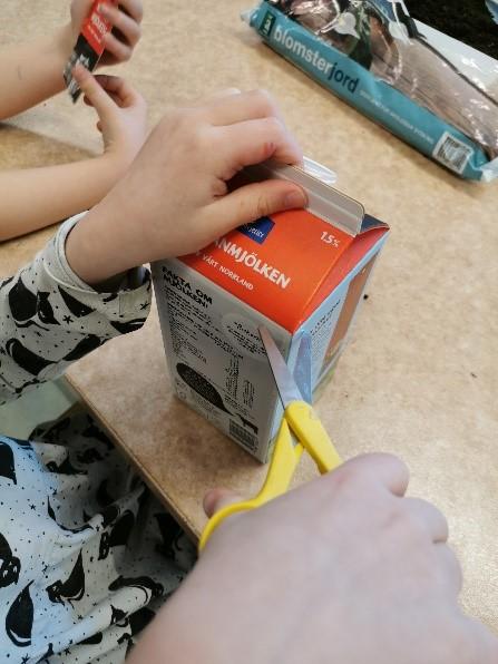Barnhänder som håller i en sax och klipper i en mjölkförpackning