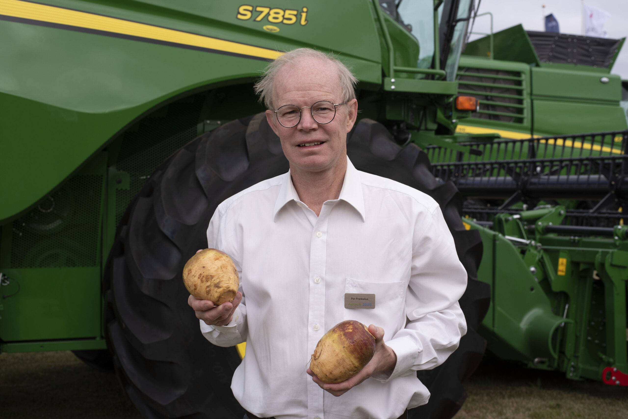 Per Frankelius står framför en grön-gul jordbruksmaskin och håller en kålrot i varje hand