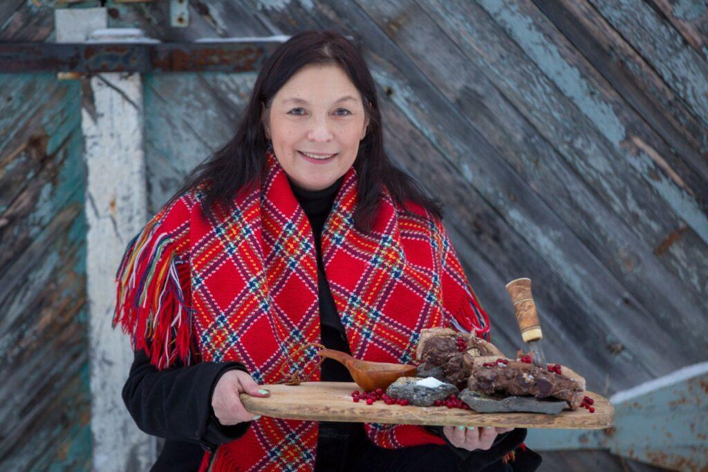Victoria Harnesk håller upp en skärbräda med renkött på